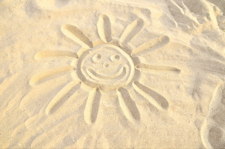 sun symbol drawn in the sand, smiling face, smiley  yellow sand, sunny day