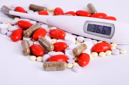 red, white, yellow, pink, brown pills and thermometer close-up on the light background
