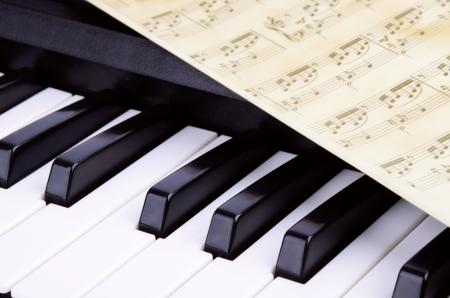 fortepian: oktawę, piano keys zbliżenie. arkusz z nutami leżącego na szczycie fortepian Zdjęcie Seryjne