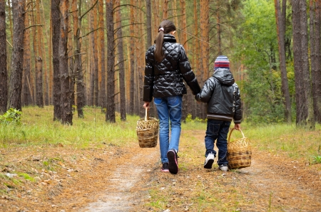 a boy and a girl are on a forest path for mushrooms. children hold baskets in their hands. shot from behind Stock Photo