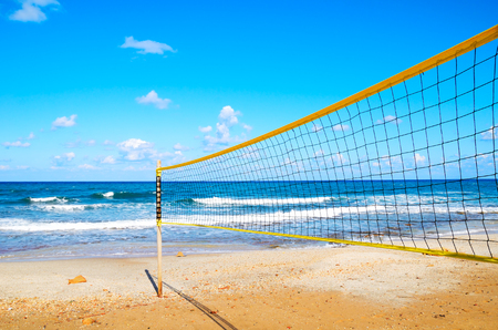 volleyball net on the beach close-up. blue cloudy sky and yellow sand on the beach photo