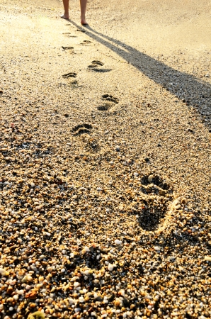 footprints in the sand at sunset time. mens feet going away Stock Photo