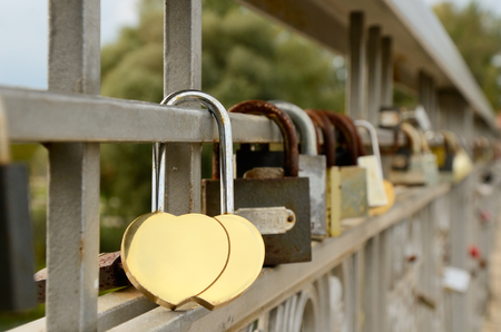 many locks hangs on a lattice bridge  lock in the shape two golden hearts