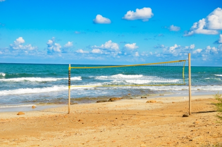 volleyball net on the beach  cloudy blue sky and turquoise sea photo