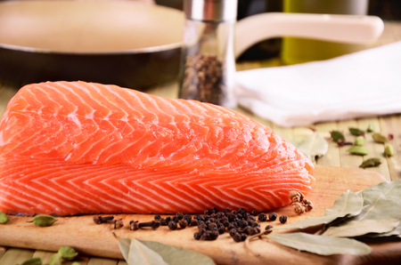 sturgeon: salmon fillet and a frying pan on the table. horizontal