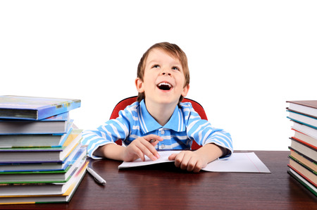 boy 5-6 years laughing while sitting at the desk  isolated on white background  horizontal Stock Photo