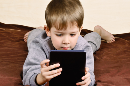 little boy 5 years lying and playing on a tablet. horizontal