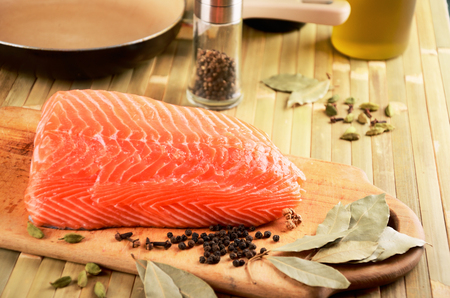 salmon fillet on a cutting board on the table. on the table cookware and spices. horizontal