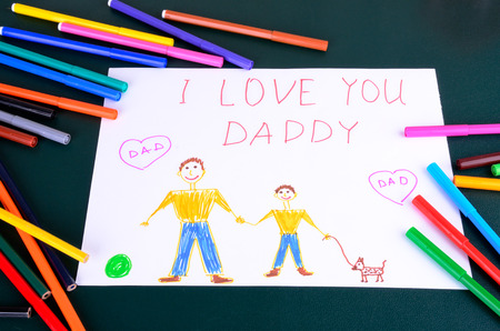 childs drawing Daddy, I love you and a lot of colored pencils and markers on the table photo