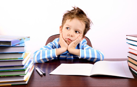 Pensive little boy sitting at a desk. on the table are many books and a notebook. ruffled the boys hair. he holds his head. on a light background. horizontal Stock Photo