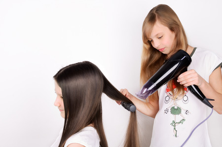 girl dries hair the hair dryer. two girls on the light background, horizontal Stock Photo
