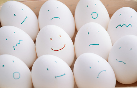 white eggs with different emotions  in tray horizontal on the full backgrpound close-up