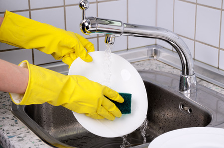 Womans hands in the gloves wash plate horizontal closeup