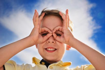 smiling boy did fingers like binoculars and looks through them  horizontal Archivio Fotografico