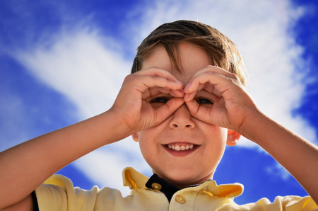 smiling boy did fingers like binoculars  horizontal