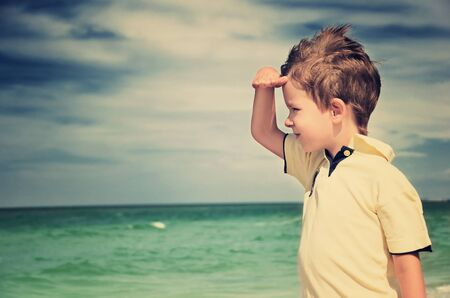 toned image boy looking away from his palm on the background of cloudy sky and sea. horizontal Stock Photo