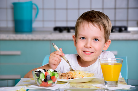 children breakfast: Smiling joyful boy sitting at the dinner table and looking at the camera. horizontal