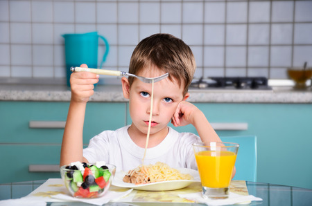 sad little boy sits at the dining table and looking spaghetti. horizontal