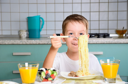 cheerful boy sits at the dining table and looking spaghetti. horizontal