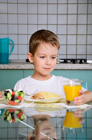 Smiling boy having dinner at the table and takes a glass of orange juice to drink. horizontal photo