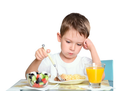 sad little boy sits at the dining table and looking in the plate. isolated on white background. horizontal photo
