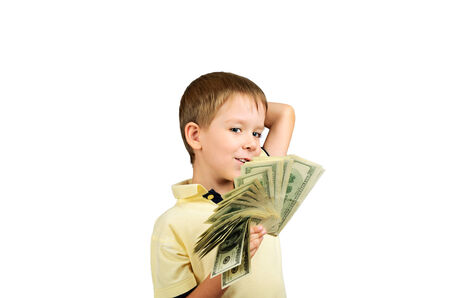 smiling boy looking at a stack of 100 US dollars bills and think what to do. isolated on white background