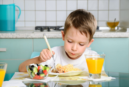 boy eating at the table, looking at the plate horizontal, holding a fork photo