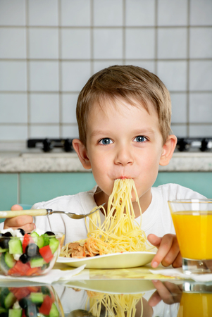 smiling boy eating spaghetti and holding the fork vertical