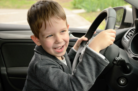 smiley face car: smiling cheerful little boy driving horizontal Stock Photo