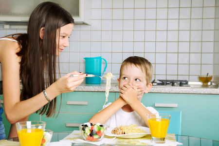 smiling girl trying to feed little boy. he closed mouth by the hands.horizontal photo