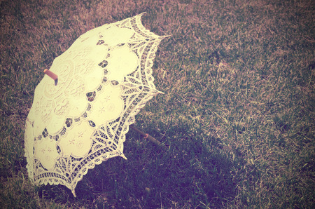 lacy parasol on the grass. tinted vintage. horizontal Stockfoto
