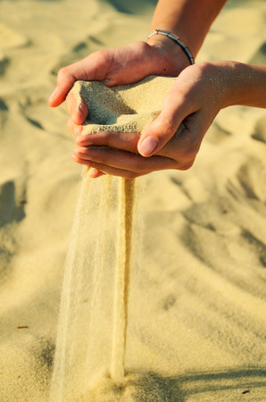 sand pours out of the female hands. horizontal