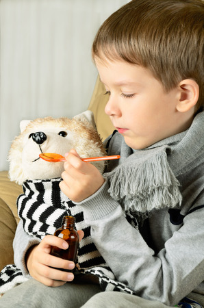 cold virus: little boy feeds medicinal syrup the toy dog. vertical Stock Photo