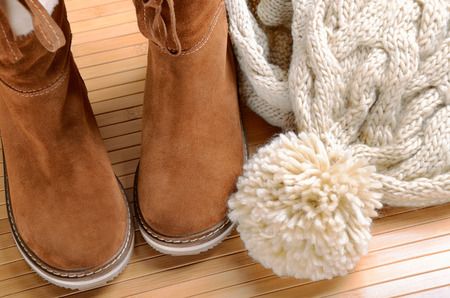 winter woman: winter boots, hat and scarf on the floor horizontal