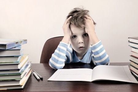 boy sitting: tinted image tired boy sitting at a desk and holding hands to head horizontal Stock Photo