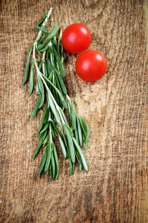sprigs: sprigs of rosemary and two cherry tomatoes on a wooden board. top view, vertical format