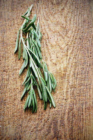 sprigs: sprigs of rosemary on a wooden board top view vertical format Stock Photo