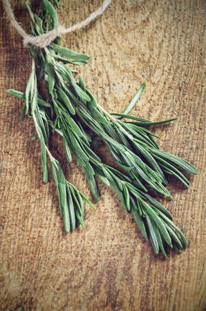toning effect sprigs of rosemary on a wooden board closeup horizontal low angle view Stock Photo