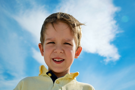 5 6 years: little boy looks down on blue cloudy sky background horizontal