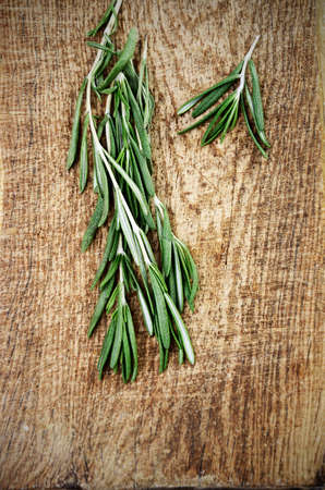 sprigs: two sprigs of rosemary on a wooden board top view vertical