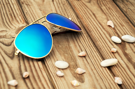 mirrored: blue mirrored sunglasses and shells on the wooden background close up. horizontal