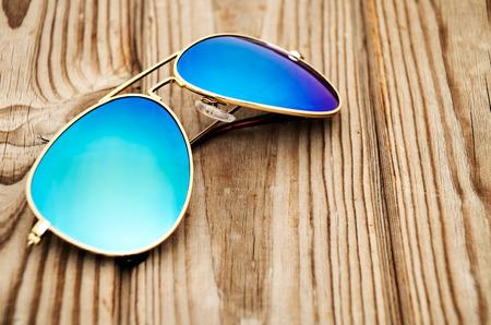 sunglasses: azul reflejado gafas de sol en el fondo de madera de cerca. horizontal