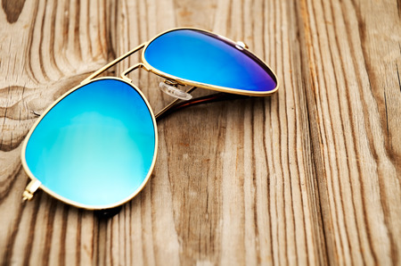 sun protection: blue mirrored sunglasses on the wooden background close up. horizontal Stock Photo