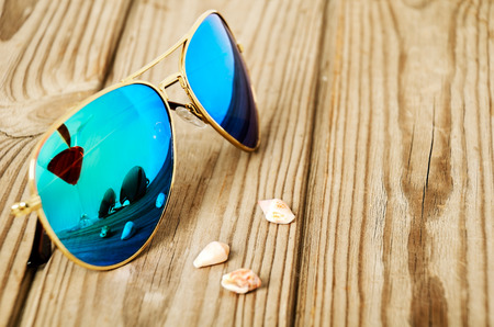 blue mirrored sunglasses wiht reflection of martini glass and shells on the wooden background close up. horizontal