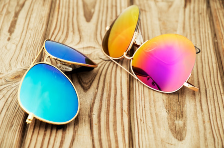 two colored sunglasses close up on the wooden background. horizontal