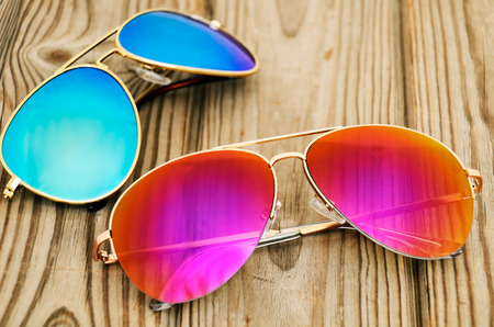 two colored sunglasses on the wooden background. horizontal
