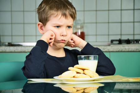 1 person: Angry little boy sitting at the dinner table. biscuits on the table and a glass of milk. the boy did not want to eat the food. green and gray kitchen furniture in the background. horizontal