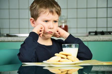 ni�os desayuno: Ni�o peque�o enojado que se sienta en la mesa de la cena. galletas en la mesa y un vaso de leche. el ni�o no quiere comer la comida. muebles de cocina verde y gris en el fondo. horizontal Foto de archivo