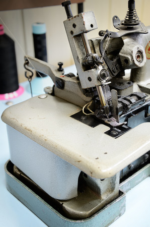 needlewoman: overlock sewing machineon the work table close up. vertical Stock Photo