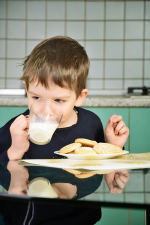 a little dinner: cheerful little boy drinking milk, sitting at the dinner table. biscuits on the table and a glass of milk. green and gray kitchen furniture in the background. vertical